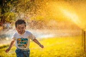 Child having a ball playing in fountain